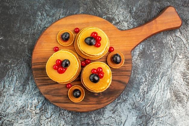 Close-up van stapel lekkere pannenkoeken op snijplank op grijs