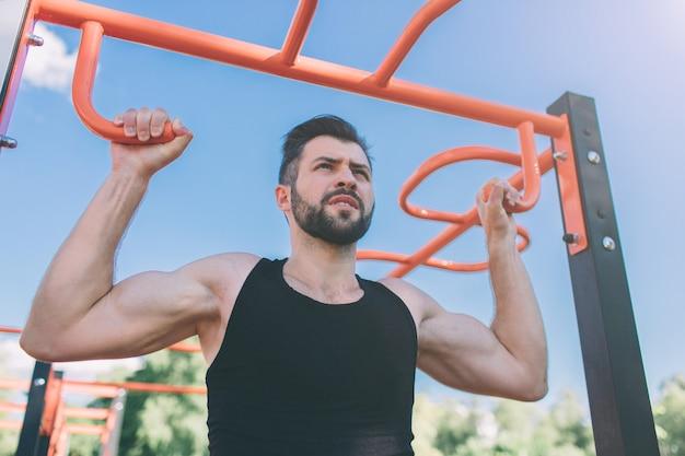 Close-up van sterke atleet doen pull-up op rekstok. mens fitness met blauwe lucht in de muur en open ruimte om hem heen. jonge man met sportieve kleding in de stad.