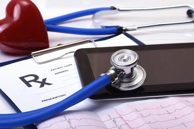 Close-up van stethoscoop op een rxrecept, een rood die hart en een telefoon op witte achtergrond wordt geïsoleerd.