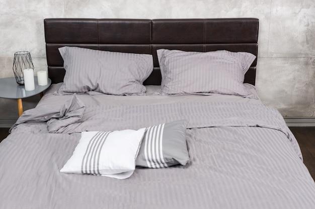 Close up van stijlvol bed met grijze kleuren en nachtkastje met kaarsen