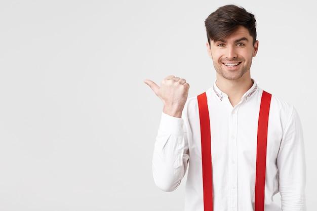 Close-up van stijlvolle aantrekkelijke man in wit overhemd en rode bretel wijzend opzij met een aangename glimlach