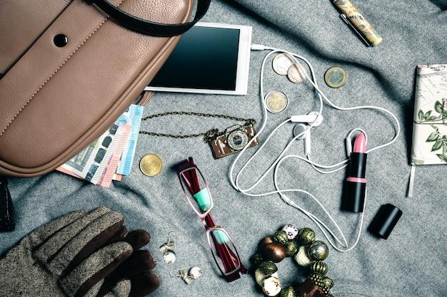 Close up van stijlvolle accessoires van vrouwelijke handtas over grijze achtergrond. uitzicht van boven.