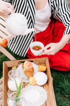 Close up van stijlvolle vrouw gieten thee in witte kop, lentetuin picknick