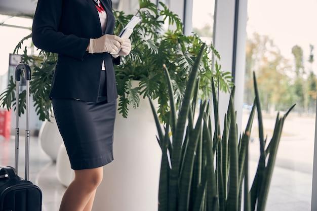 Close up van stijlvolle vrouw in steriele handschoenen met smartphone en instapkaart tijdens het wachten op haar vlucht op de luchthaven