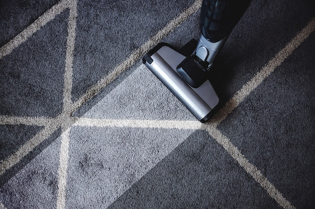Close-up van stoomreiniger die erg vuil tapijt schoonmaakt.