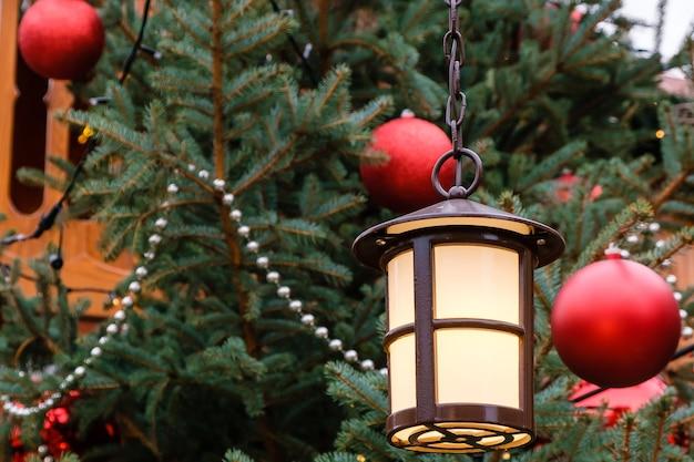 Close-up van straatlantaarn en rode kerstballen met led-slinger op versierde natuurlijke nieuwjaarsboom op een feestelijke kerstmarkt op centrale stadsstraat. selectieve aandacht voor een lamp.