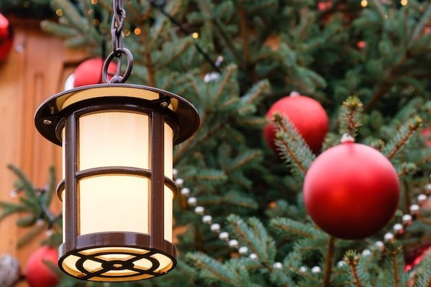 Close-up van straatlantaarn en rode kerstballen met led-slinger op versierde natuurlijke nieuwjaarsboom op een feestelijke kerstmarkt