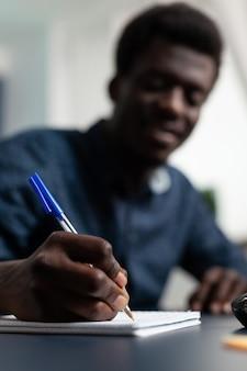 Close-up van student die marketingstrategie op notitieboekje schrijft
