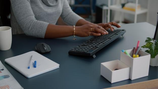 Close-up van student met zwarte huidhanden die op toetsenbord typen die informatie zoeken