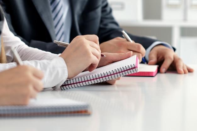 Close-up van studenten of zakenmensen handen iets schrijven tijdens de conferentie. zakelijke bijeenkomst, bloggen of professioneel onderwijs concept