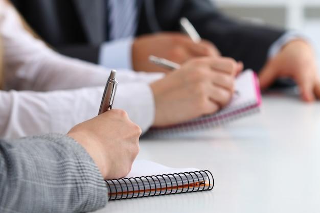 Close-up van studenten of zakenmensen handen iets schrijven tijdens de conferentie