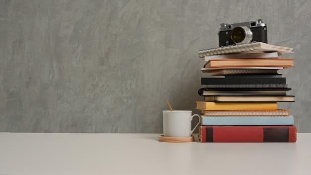 Close-up van studie tafel met stapel boeken camera cup en kopieer de ruimte in de woonkamer