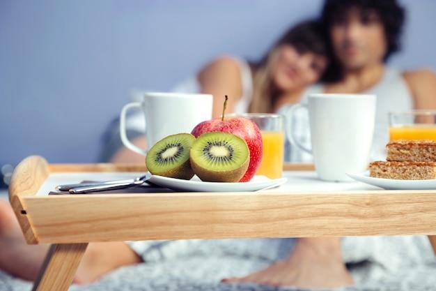 Close-up van stukjes fruit in een gezond ontbijt geserveerd op dienblad en een gelukkig verliefd paar knuffelen. gezond eten en home lifestyle concept.