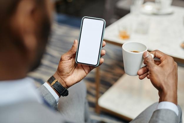 Close-up van succesvolle afro-amerikaanse zakenman die smartphone met leeg scherm vasthoudt terwijl hij geniet van koffie in café, kopieer ruimte