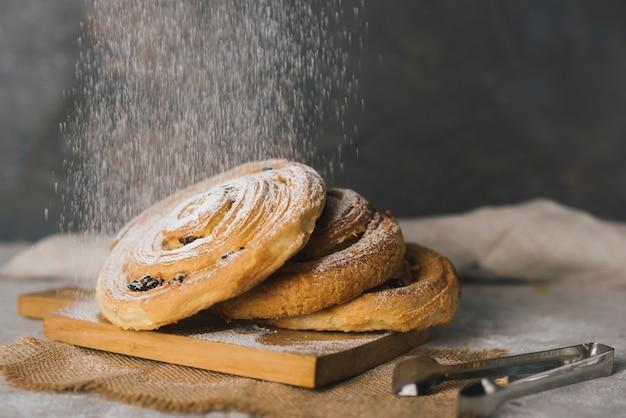 Close-up van suiker afstoffen op gebakken kaneel broodjes over het snijplank