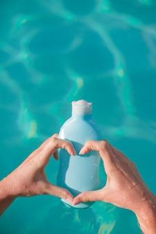 Close-up van sunblock in vrouwelijke handen bacjground de pool