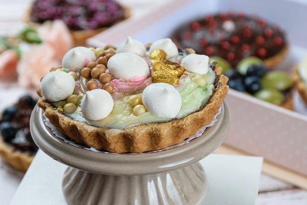 Close-up van taart met boterachtig deeg gevuld met chocolade ganache. omhuld met pistachecrème, gedecoreerd met meringue, pistachenoten en witte chocoladeballetjes en gezouten karamel.