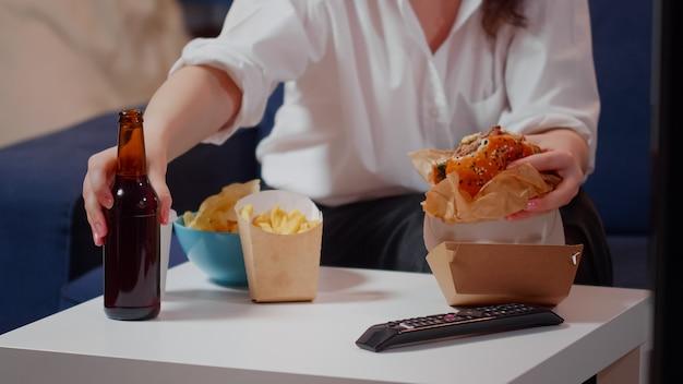 Close up van tafel met levering fastfood en persoon aan het eten