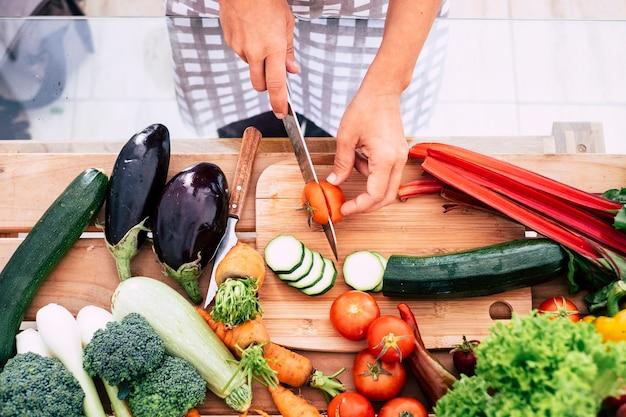 Close-up van tafel vol groenten zoals tomaten, wortelen en meer