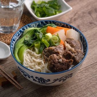 Close-up van taiwanese beroemde gerechten met gesneden gestoofde rundvlees schenkel en groenten in een kom op houten tafel