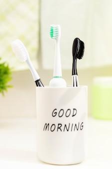 Close-up van tandenborstels in een glas op het aanrecht in de badkamer op een zonnige ochtend.