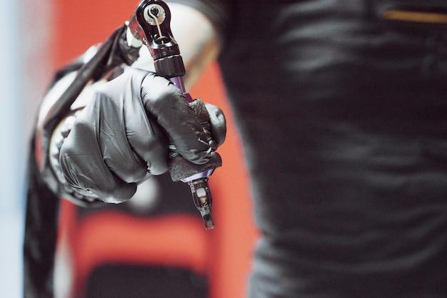 Close-up van tattoo machine. meester in zwarte steriele handschoenen die beeld bij de hand in salon creëren