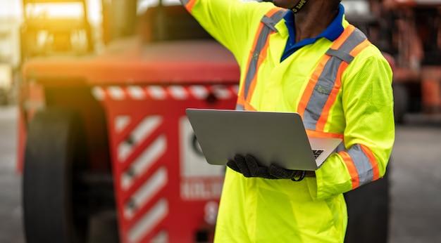 Close-up van technicus dokwerker in beschermende uniforme veiligheid jumpsuit en met veiligheidshelm en laptopcomputer gebruiken bij lading container verzending magazijn. transport import, export logistiek industrieel