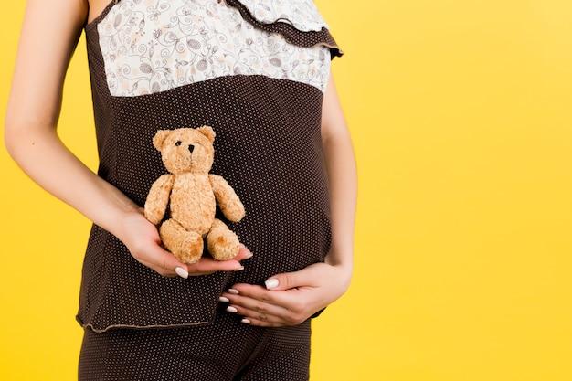 Close up van teddybeer in de hand van de zwangere vrouw op gele achtergrond. toekomstige moeder draagt een bruine pyjama. moederschap concept. ruimte kopiëren.