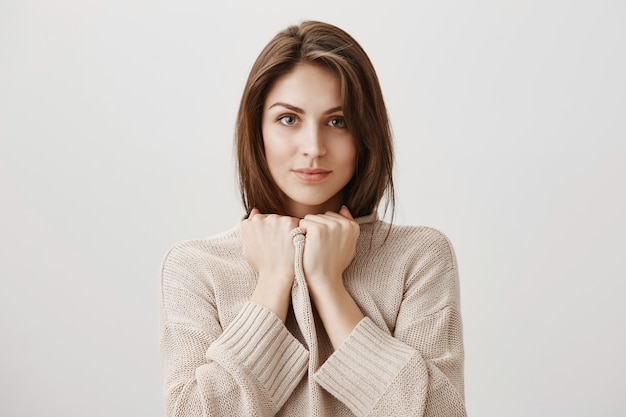 Close-up van tedere vrouw die gezellig in trui voelt
