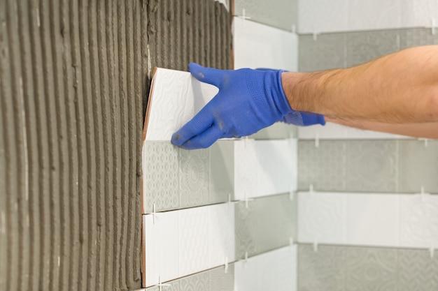 Close-up van tegelzetterhand die keramische tegel op muur in keuken leggen