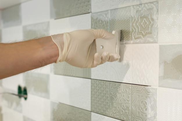 Close-up van tegelzetterhand die tegel wrijven, installeren en voegen decoratieve afwerkingen