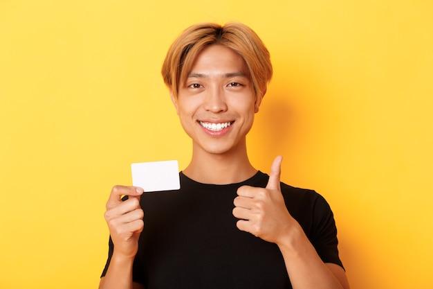 Close-up van tevreden aziatische kerel raadt bank aan, creditcard toont en zich over gele muur bevindt