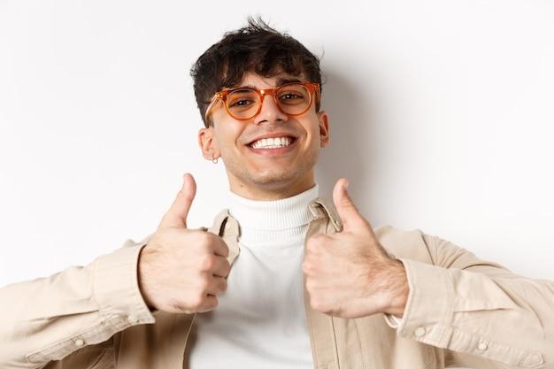 Close-up van tevreden gelukkige kerel die duimen toont en met witte tanden glimlacht, die een bril draagt, die zich op witte muur bevindt.