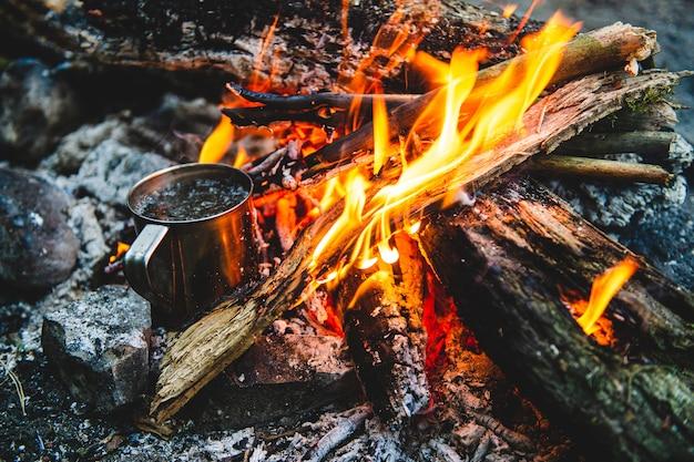 Close-up van thee in metalen mok warmt op in vreugdevuur
