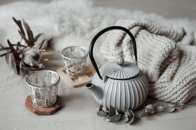 Close-up van theepot in scandinavische stijl met thee met gebreid element en decordetails