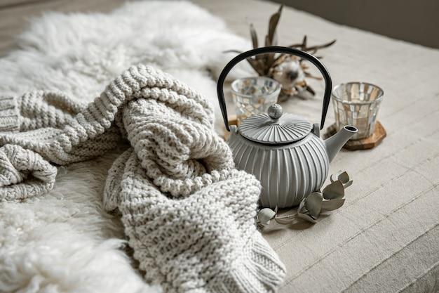 Close-up van theepot in scandinavische stijl met thee met gebreid element en decordetails.