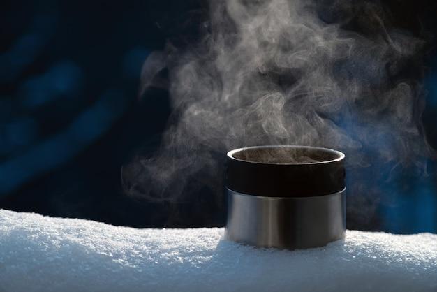 Close up van thermos beker met hete dampende drank buiten in de sneeuw. niemand