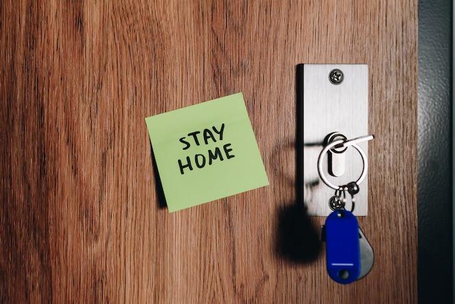 close up van thuis blijven kleverige handgeschreven notitie op voordeur naast sleutels en slot, voorzorgs- en preventiemaatregel om geïsoleerd te blijven tijdens wereldwijde coronavirus covid-19 pandemie en quarantaine