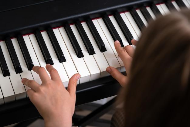 Close-up van tienerhanden die piano spelen in de thuismuziekstudio