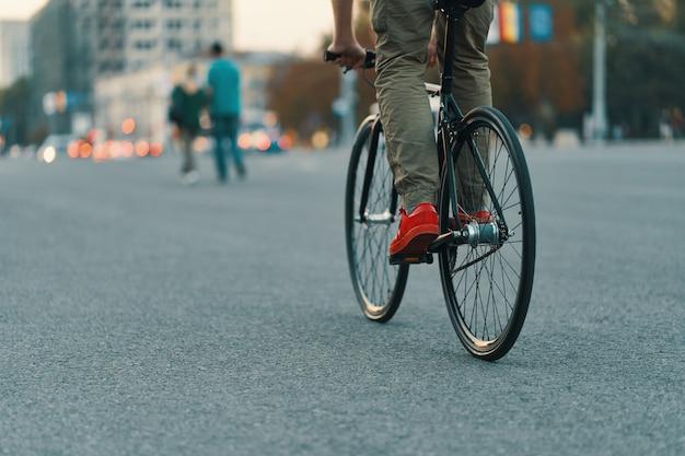 Close-up van toevallige mensenbenen die klassieke fiets berijden op stadsweg