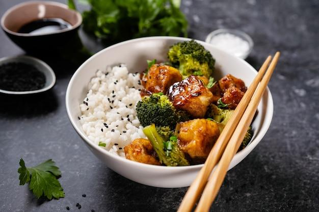 Close-up van tofu kom met rijst en broccoli op zwarte achtergrond