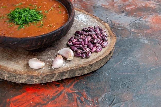 Close-up van tomatensoep bonen knoflook op houten snijplank op mix kleurentafel