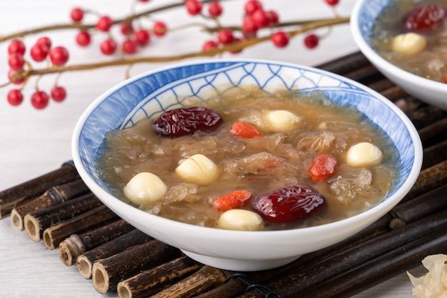 Close-up van traditionele chinese zoete sneeuwwitte schimmelsoep met lotuszaad, rode dadels (jujube) en wolfberry (gojibes, gojibes) op wit