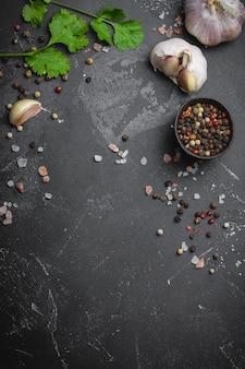 Close up van traditionele kookingrediënten: knoflook, olijfolie, zout, peper, verse kruiden op donkere rustieke achtergrond. voedselframe, concept voor het koken van gezond voedsel met ruimte voor tekst, bovenaanzicht