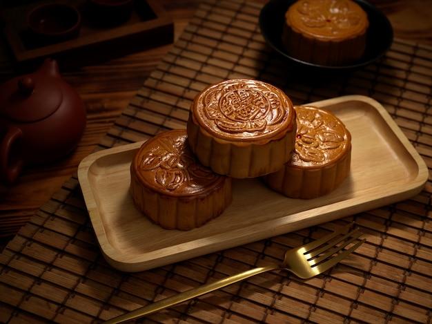 Close-up van traditionele maancakes op houten plaat met vork en theeservies. chinees karakter op de maancake vertegenwoordigt