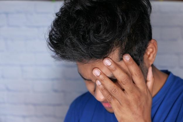 Close up van trieste man die betrekking heeft op gezicht met de hand.
