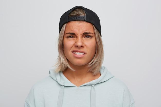 Close-up van trieste ongelukkige blonde jonge vrouw met beugels aan de tanden draagt zwarte pet en hoodie kijkt boos en ontevreden geïsoleerd over witte muur