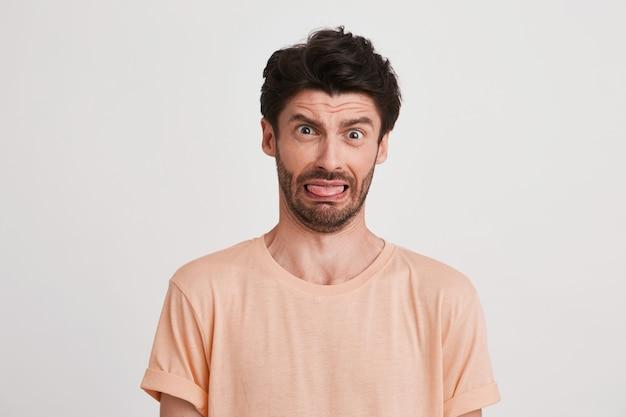 Close-up van trieste ontevreden jonge man met borstelharen draagt perzik t-shirt voelt ontevreden en fronst zijn gezicht geïsoleerd op wit