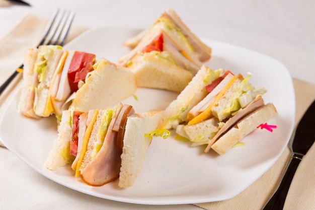 Close up van triple decker sandwich op plaat bij couvert