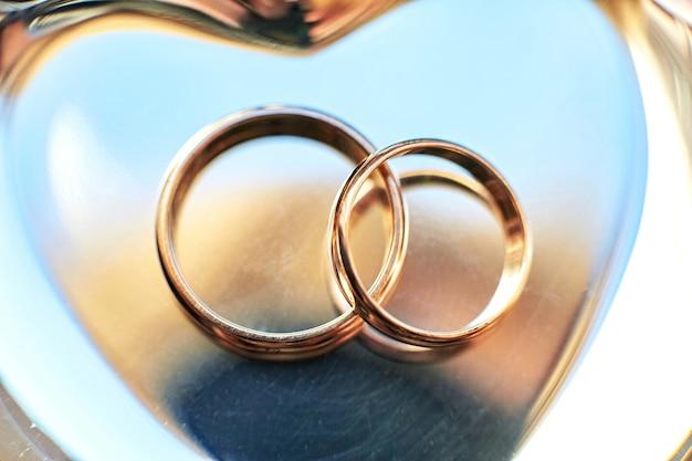Close-up van trouwringen die op de gouden plaat liggen
